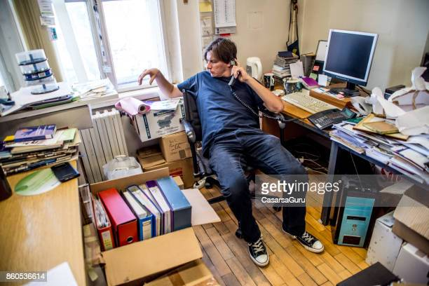 entrepreneur talking on phone in messy office - messy stock pictures, royalty-free photos & images