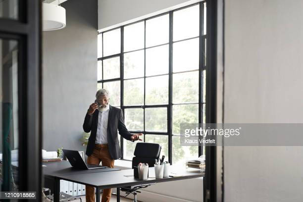 entrepreneur talking over phone in modern office - focus on background stock pictures, royalty-free photos & images