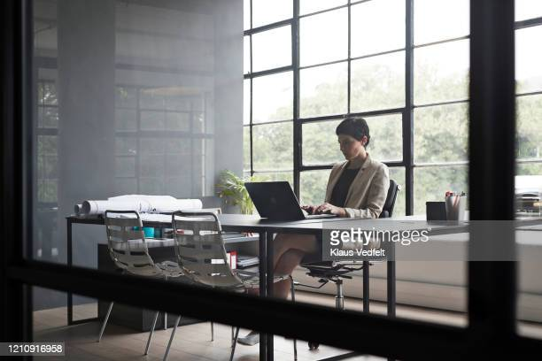 entrepreneur typing over laptop in modern office - cream coloured blazer stock pictures, royalty-free photos & images