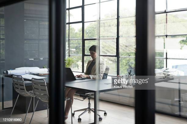 entrepreneur using laptop at workplace - cream coloured blazer stock pictures, royalty-free photos & images