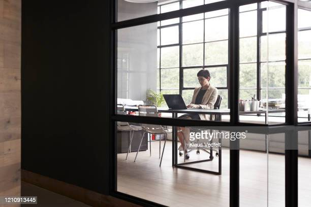 entrepreneur using laptop in modern office - cream coloured blazer stock pictures, royalty-free photos & images