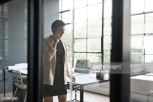 entrepreneur using mobile phone at new workplace - cream coloured blazer stock pictures, royalty-free photos & images