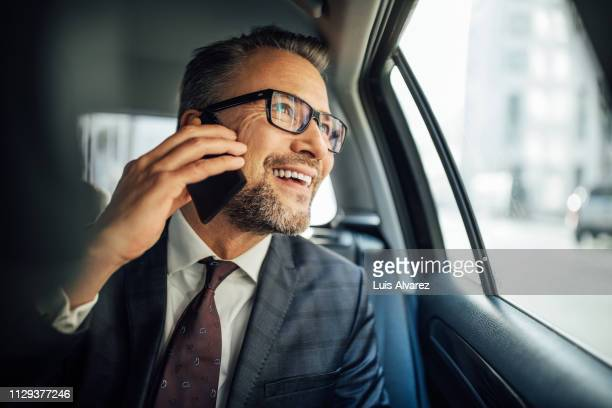 entrepreneur using phone while traveling by a car - geschäftsmann stock-fotos und bilder