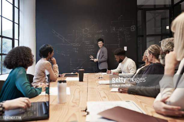 entrepreneur with coworkers in conference room - diversity stock pictures, royalty-free photos & images