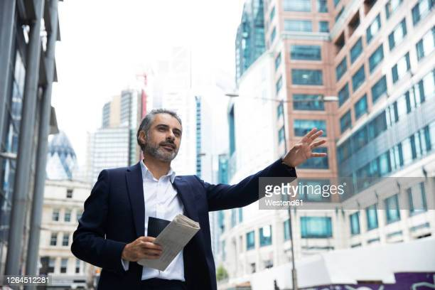 entrepreneur with cup and newspaper hailing taxi in city - three quarter length stock pictures, royalty-free photos & images