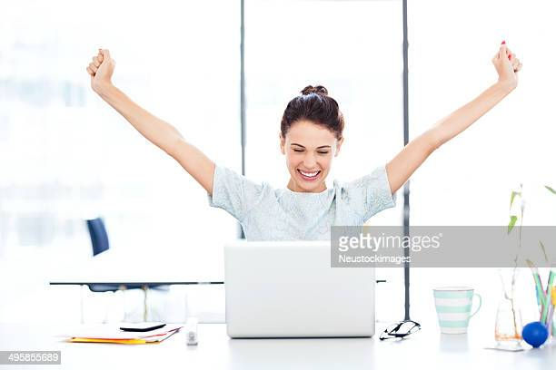 Entrepreneur With Laptop Celebrating Success At Desk