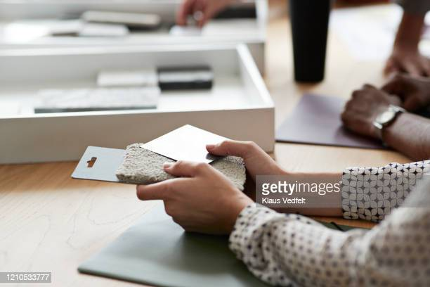 entrepreneur with samples over table in office - interior designer stock pictures, royalty-free photos & images