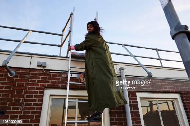woman climbs up a ladder - benelux stockfoto's en -beelden