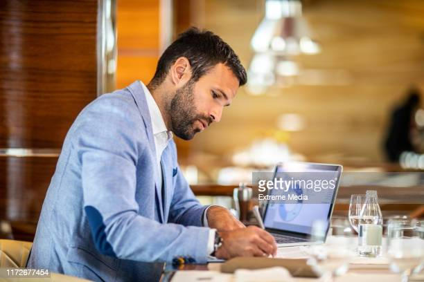 entrepreneur writing on a document while sitting in a restaurant - risk stock pictures, royalty-free photos & images