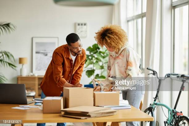 entrepreneurs analyzing packaging at table - business stock pictures, royalty-free photos & images