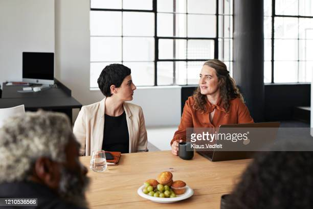 entrepreneurs discussing by table at workplace - cream coloured blazer stock pictures, royalty-free photos & images