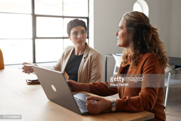 entrepreneurs discussing by table at workplace - employee engagement stock pictures, royalty-free photos & images
