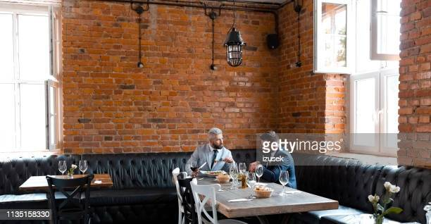 entrepreneurs discussing while having lunch in pub - artisanal food and drink stock pictures, royalty-free photos & images