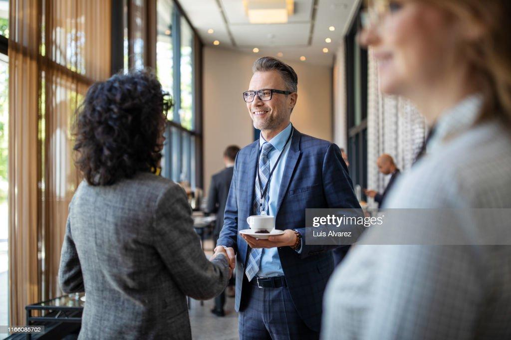 Entrepreneurs greeting each other in break at seminar : Stock Photo