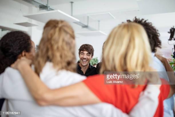 entrepreneurs huddling together in creative office - federer photos et images de collection