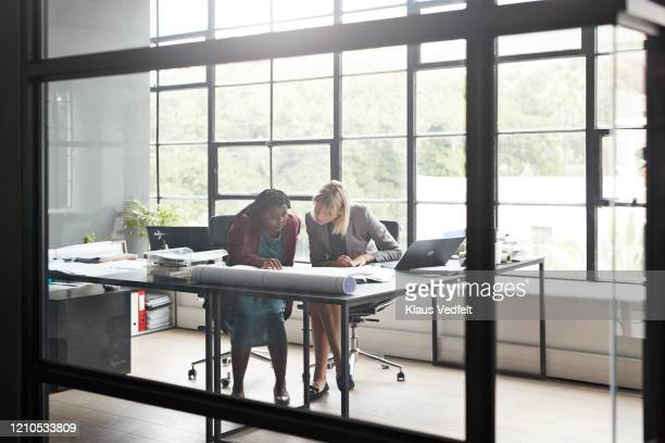 entrepreneurs looking at plan by office desk - negócios finanças e indústria - fotografias e filmes do acervo