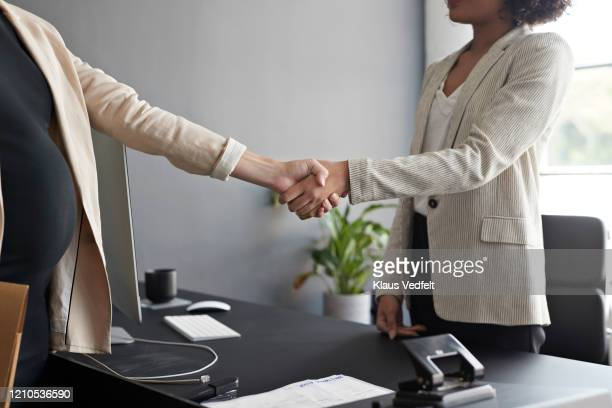 entrepreneurs shaking hands in modern office - cream coloured blazer stock pictures, royalty-free photos & images