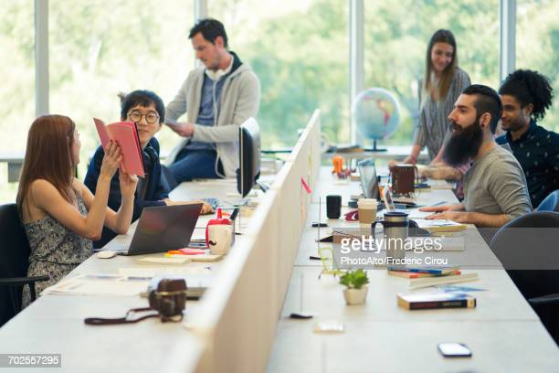 entrepreneurs working in open plan office - hot desking stock pictures, royalty-free photos & images