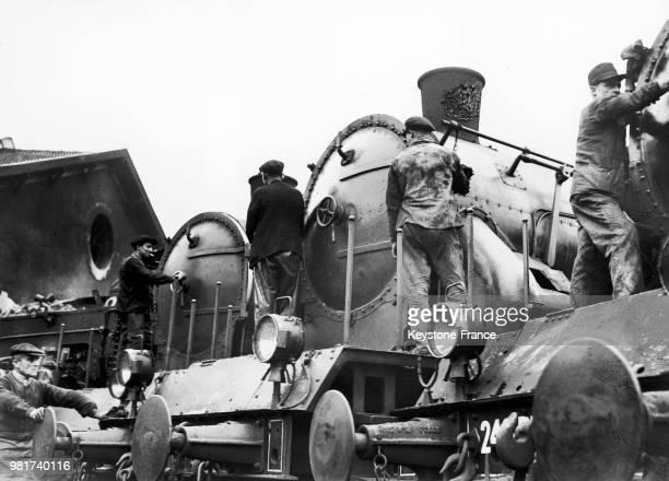 Entretien des locomotives à vapeur 230 de la compagnie du chemin de fer Paris-Lyon-Méditerranée au dépôt de la gare de Lyon à Paris en France, le 6...