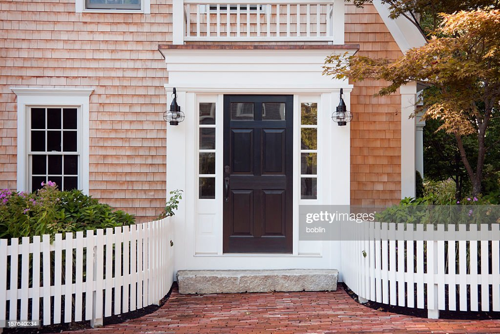 Entryway of brick New England home with picket fence : Stock Photo