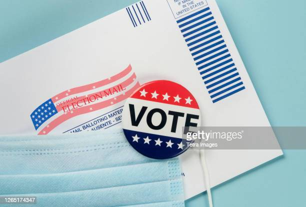 envelope, election pin and face mask against blue - voting stock pictures, royalty-free photos & images