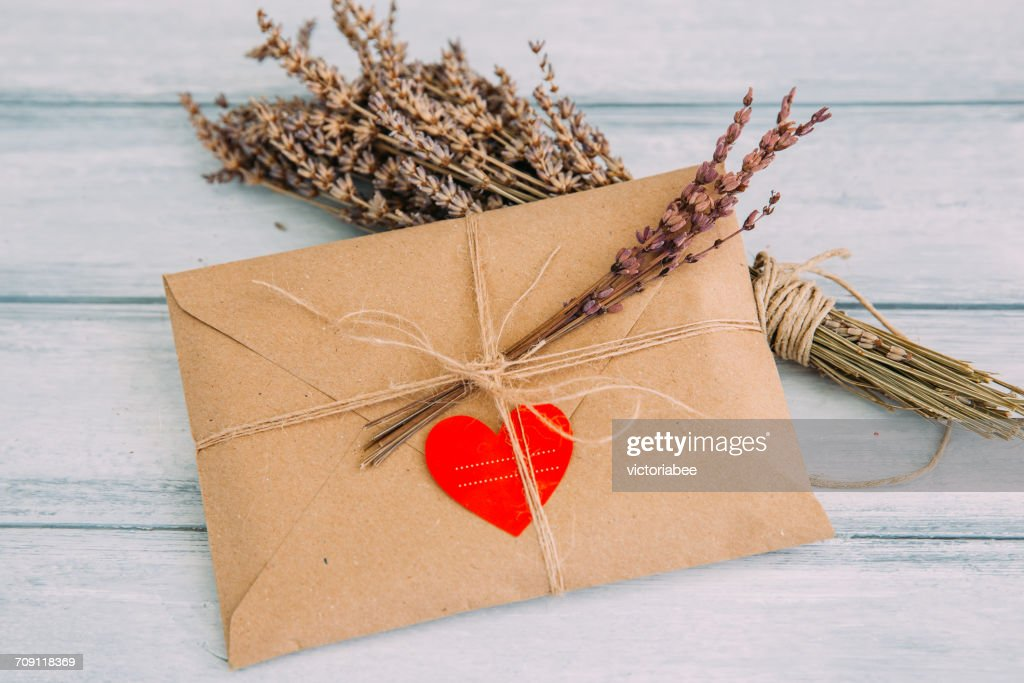 Envelope with heart sticker and dried flowers : Stock Photo