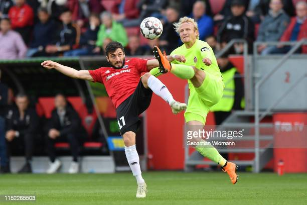 Enver Cenk Sahin of Ingolstadt and Alf Mintzel of Wehen Wiesbaden compete for the ball during the Second Bundesliga playoff second leg match between...