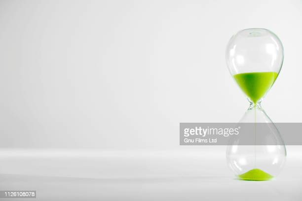 environement concept - a green hourglass filling up with sand - día fotografías e imágenes de stock