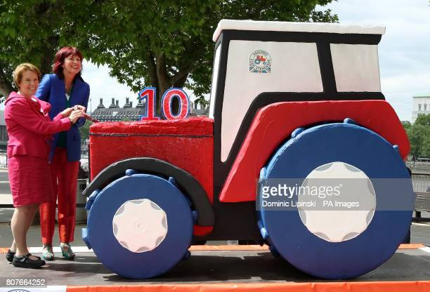 Environment Secretary Caroline Spelman and Janet Street Porter cut a giant tractor cake to mark the 10th birthday of the Red Tractor food standards...