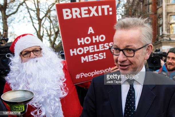 Environment Secretary Michael Gove is accosted by a protester in a Father Christmas outfit after speaking the media in Westminster on December 12...