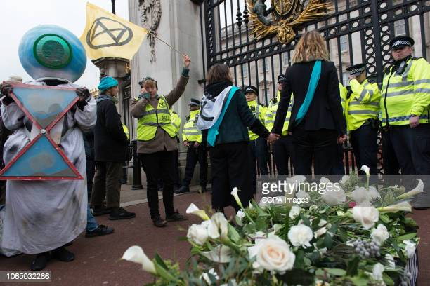 Environmental activist and police officers seen at the Buckingham Palace gate Thousands of demonstrators from the new Extinction Rebellion climate...