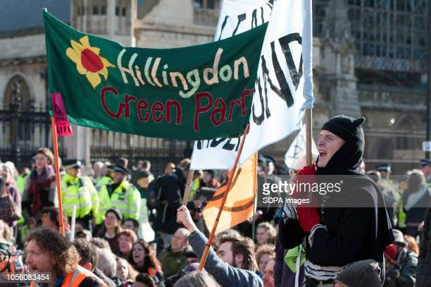 Environmental activist are seen holding banners while blocking the road outside Parliament during the protest The newly formed Extinction Rebellion...