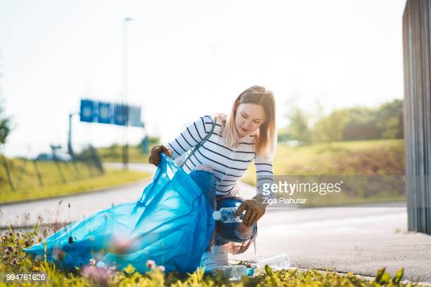 environmental activist collecting plastic garbages in nature - climate activist stock pictures, royalty-free photos & images