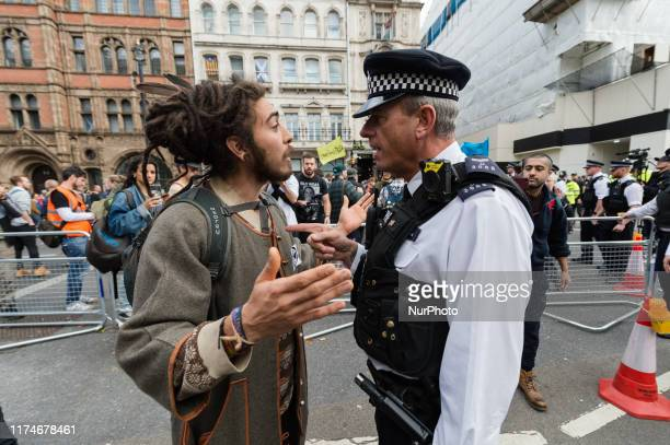 Environmental activist from Extinction Rebellion argues with police in Whitehall outside Downing Street on 08 October 2019 in London England The...