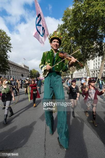Environmental activist from Extinction Rebellion walks on stilts and plays the violin in Whitehall outside Downing Street on 08 October 2019 in...