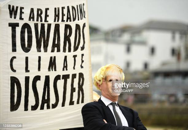 Environmental activist from Extinction Rebellion wears a face masks of Britain's Prime Minister Boris Johnson takes part in a photocall in St Ives on...