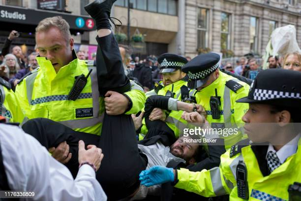 A environmental activist is arrested while protesting about Climate Change during the blockade of Whitehall in central London part of a twoweek...