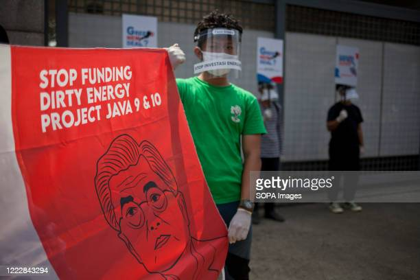 Environmental activist is seen wearing a face shield while holding a banner with a picture of South Korean President with a headline reading Stop...