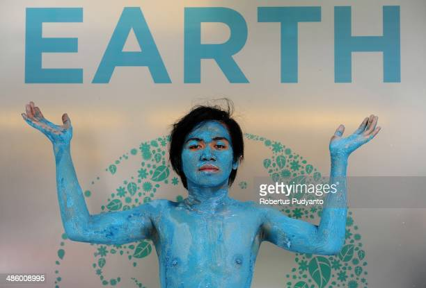 Environmental activist performs as part of an energy saving campaign during annual Earth day celebration at Surabaya University on April 22 2014 in...