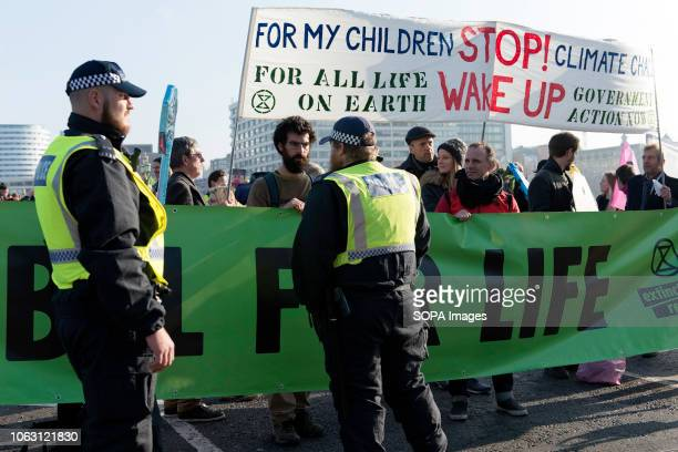 Environmental activist seen talking with a police officer Extinction Rebellion activists gathered at five main bridges in London to raise their...