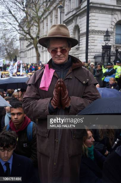 Environmental activists and protesters pause in their 'funeral' march outside Downing Street during a demonstration organised by the movement...