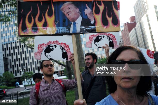 Environmental activists and supporters display placards during a demonstration in New York on June 1 to protest US President Donald Trump's decision...