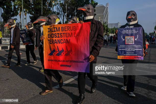 Environmental activists are seen taking action on Global Day of Action to Protect the Ocean by wearing a penguin costume in Pekanbaru Riau Province...