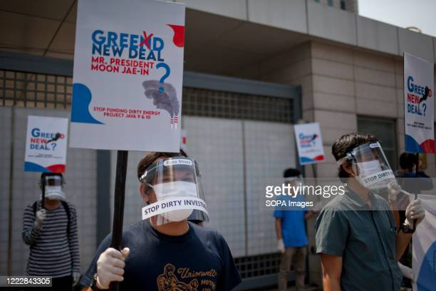 Environmental activists are seen wearing a face shields and hand gloves while holding protest signs during the AntiEnergy Rally Activists staged a...