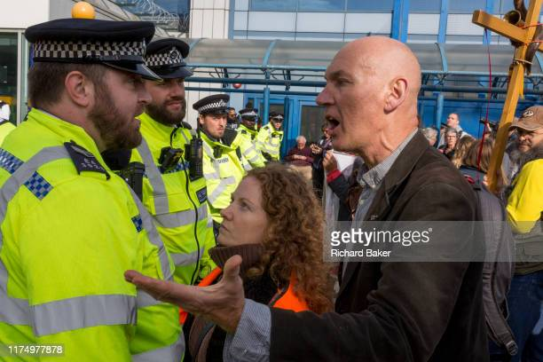 Environmental activists argue with police officers while protesting about Climate Change during the occupation of City Airport in east London the...