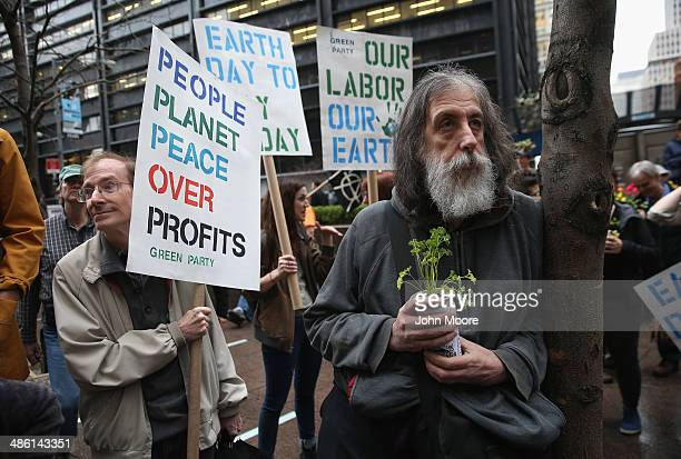 Environmental activists attend a protest in Zucotti Park on Earth Day on April 22 2014 in New York City About three dozen activists marched around...