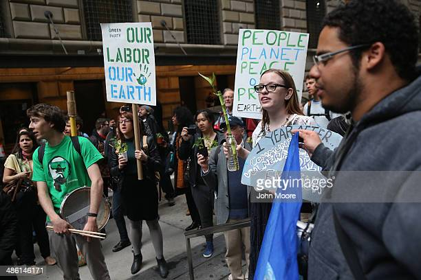 Environmental activists attend a protest on Earth Day on April 22 2014 in New York City About three dozen activists marched around New York's...