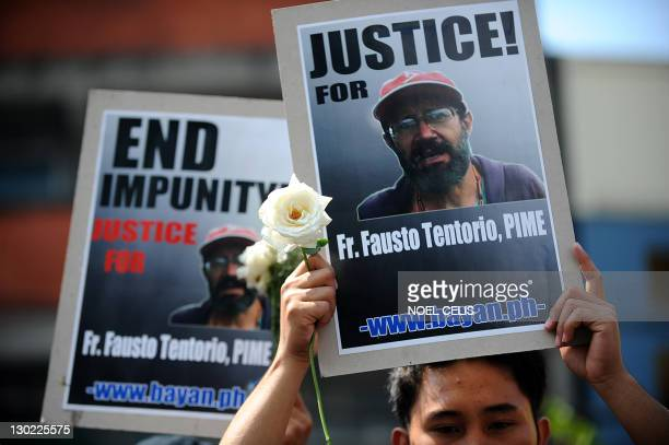 Environmental activists carry placards with pictures of murdered Italian missionary Fausto Tentorio during a protest near the Malacanang palace in...
