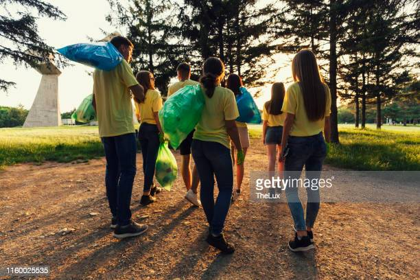 environmental activists cleaning up a city park of plastic waste - climate activist stock pictures, royalty-free photos & images