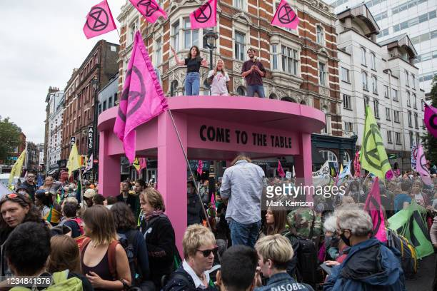Environmental activists from Extinction Rebellion gather around a giant table used to block roads in the Covent Garden area during the first day of...